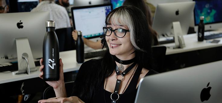 Uma jovem de óculos sentada atrás de um computador, sorri para foto enquanto segura uma garrafa onde se lê: 42 São Paulo