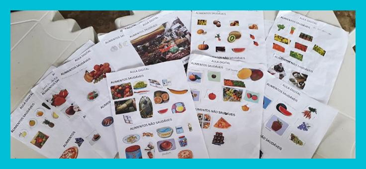 Imagem mostra diversas folhas de papel com colagens de fotos recortadas de alimentos separados pelos títulos: alimentos saudáveis e alimentos não saudáveis. Atividade faz parte de projeto sobre alimentação saudável.