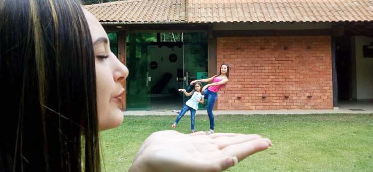 """Imagem mostra menina """"gigante"""" """"assoprando"""" duas outras meninas na mão (ilusão de perspectiva). Ao fundo se vê uma casa."""