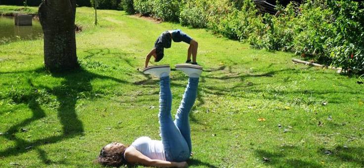 """Imagem mostra menina deitada carregando uma pessoa fazendo o movimento de """"ponte"""" sobre seus pés, em ilusão de perspectiva"""