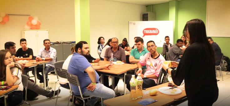 A imagem mostra um grupo de pessoas sentadas dentro de uma sala