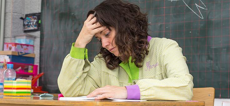 Imagem mostra uma mulher sentada atrás de uma mesa com a cabeça abaixada e uma das mãos na testa. Atrás dela é possível ver uma lousa com um desenho feito de giz