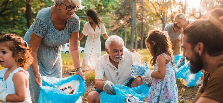 Imagem mostra grupo de pessoas fazendo trabalho voluntário. Crianças, adultos e idosos seguram sacos plásticos, enquanto recolhem o lixo (latas e garrafas)
