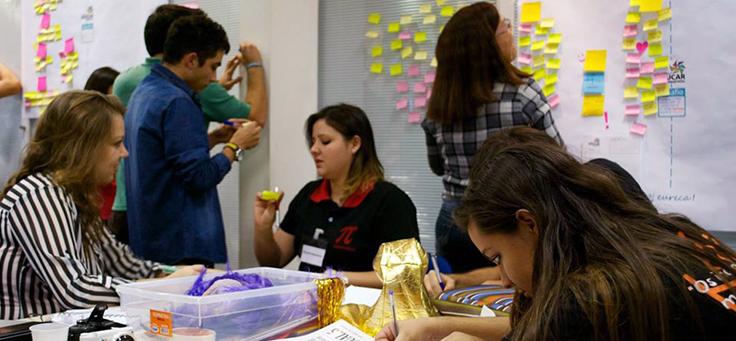 Na imagem estudantes da Academia Educar, que contribui para a formação de jovens, estão montando quadros com ajudas de materiais como post-its.