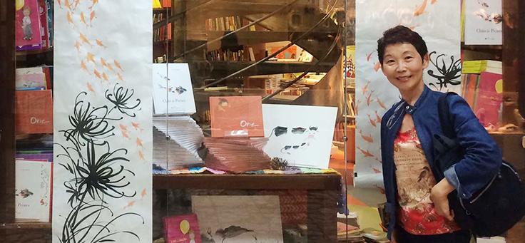 A escritora Lúcia Hiratsuka posa para foto em frente à vitrine de uma livraria