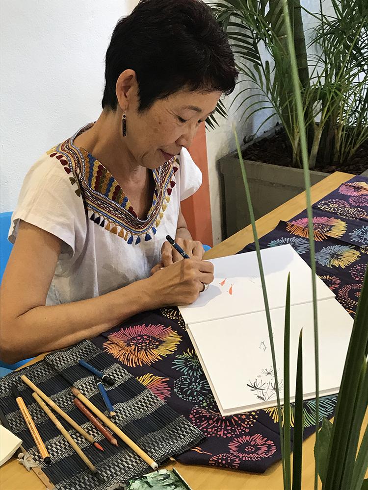 Imagem da escritora Lúcia Hiratsuka desenhando em um caderno