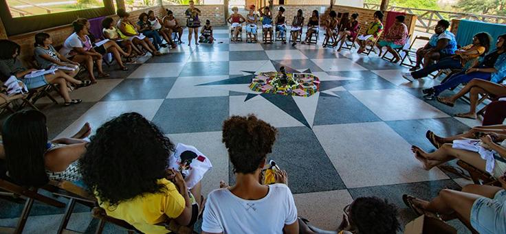 Cerca de 20 mulheres jovens e adultas estão sentadas em roda em um galpão com grandes janelas na Uneafro, iniciativa que contribui para a formação de jovens.