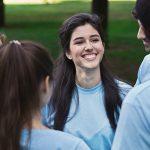 Imagem mostra um grupo de pessoas usando camisetas azuis formando um círculo em um parque