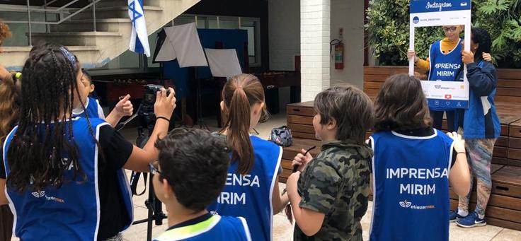 """Imagem mostra grupo de crianças de costas usando aventais azuis onde se lê """"Imprensa Mirim"""", usando câmeras fotográficas. Duas delas está de frente segurando uma moldura como se fosse da rede social Instagram."""