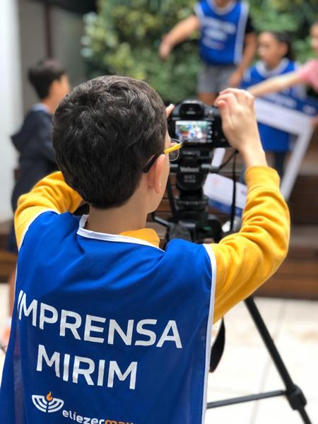 """Imagem mostra aluno tirando fotos com uma câmera posicionada sobre um tripé. Ele usa um avental onde se lê """"Imprensa Mirim""""."""