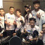 Imagem mostra um grupo de crianças e adultos posando para foto em grupo dentro de um estúdio de som, onde se vê microfones e alguns equipamentos sobre a mesa