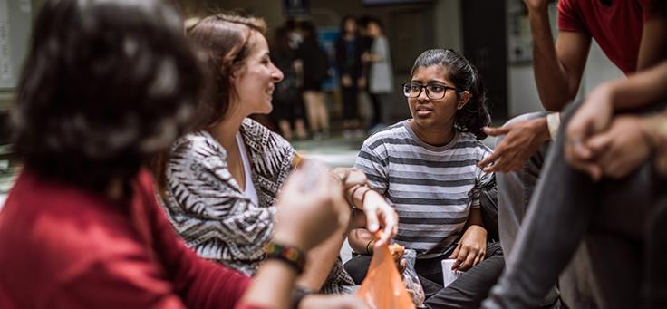 Imagem mostra três pessoas jovens sentadas conversando