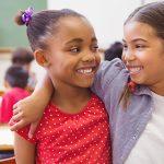 A imagem mostra duas meninas abraçadas e sorrindo uma para outra dentro de uma sala de aula