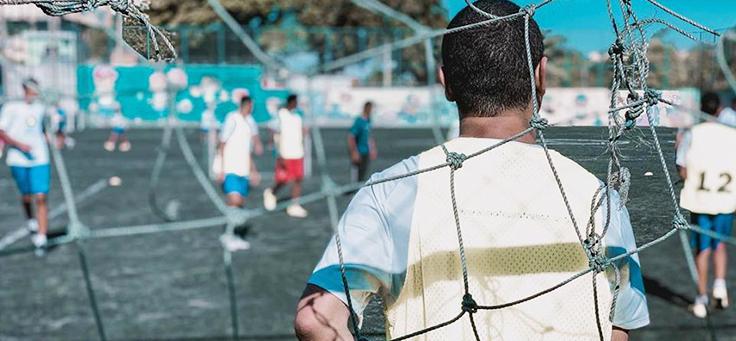 Imagem mostra meninos de uniforme em um campo de futebol
