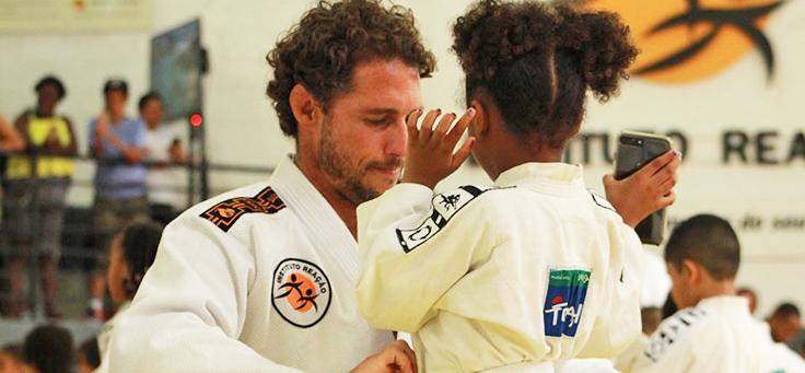 Imagem mostra o ex-judoca Flávio Canto e uma criança de costas usando quimonos