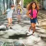 Imagem mostra três crianças de mochila nas costas brincando sob uma calçada com um caminho de giz desenhado
