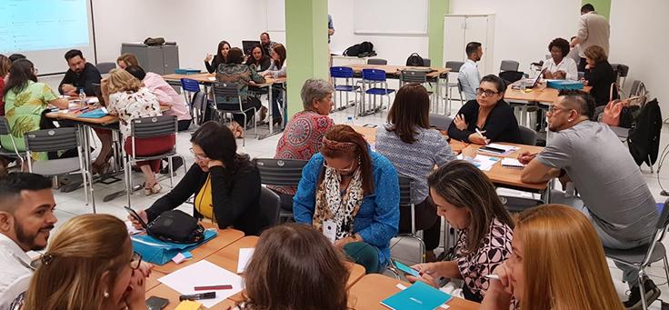 Técnicos de secretarias de educação de vários estados estão sentados em grupos e participam de oficina sobre futurologia e novo ensino médio durante evento do Consed.