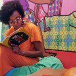 Imagem mostra mulher lendo livro. Ela está sentada sobre almofadas coloridas.