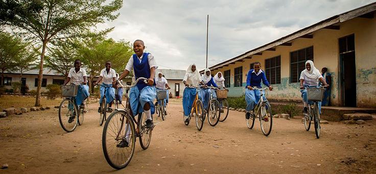 Imagem mostra um grupo de crianças uniformizadas andando de bicicleta em um chão de terra