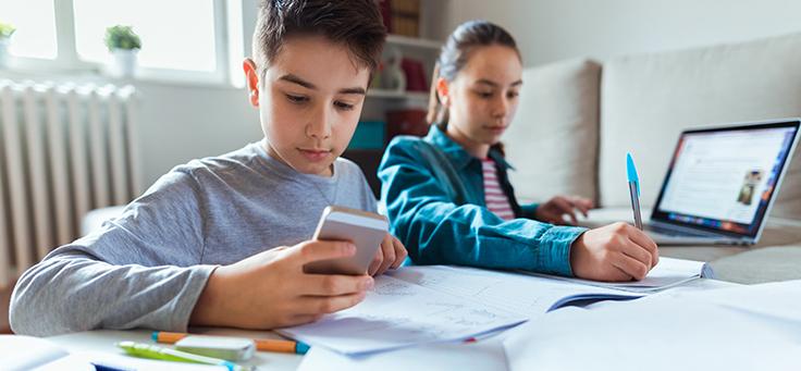 Imagem mostra um menino e uma menina sentados atrás de uma mesa em que há papeis espalhados