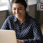 Mulher sorri e olha para tela de notebook enquanto usa fones de ouvido para ilustrar exemplos de boas práticas na educação a distância.
