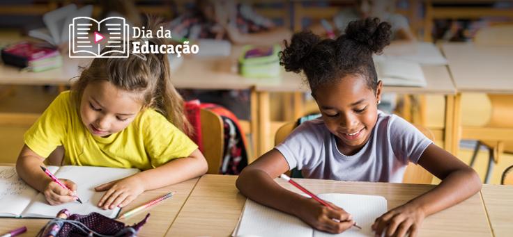 Imagem mostra duas meninas em destaque dentro de uma sala de aula. Elas estão sentadas uma ao lado da outra, escrevendo em cadernos.