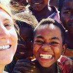 Imagem mostra Iara Xavier, do Caçadores de Bons Exemplos, abraçada com crianças. Todos sorriem para a câmera.