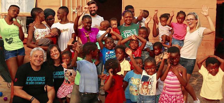 Imagem mostra Iara e Eduardo Xavier, do Caçadores de Bons Exemplos, em grupo com diversas pessoas. Todos sorriem para a câmera.