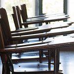 A imagem mostra carteiras vazias em uma sala de aula