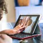 Imagem mostra uma menina colocando a mão na tela de um tablet