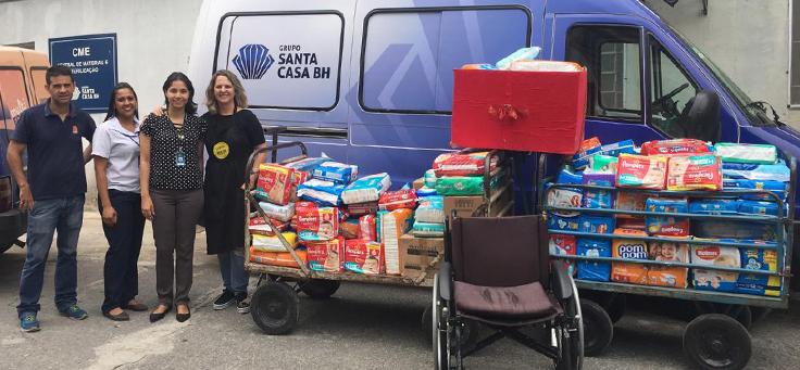 A imagem mostra uma das ações solidárias, em que integrantes do grupo Marias Bonitas estão posando ao lado de alimentos e outros itens para a Santa Casa de Belo Horizonte.