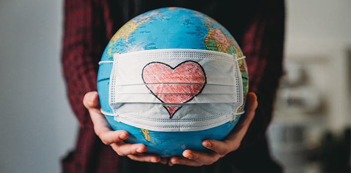 Imagem mostra duas mãos segurando o globo terrestre que está com uma máscara com desenho de coração